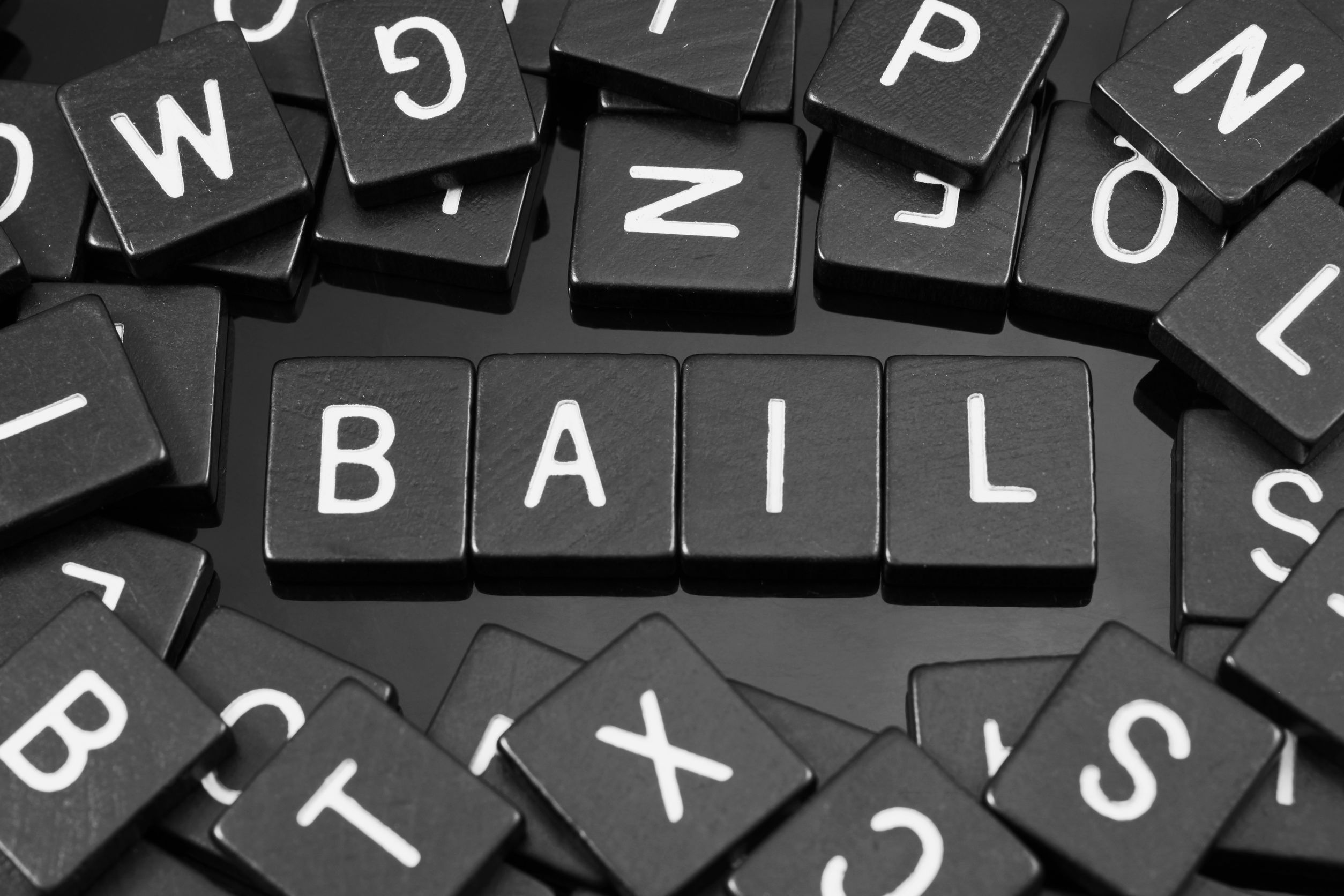 "black letter tiles spelling the word ""bail"" on a reflective background"