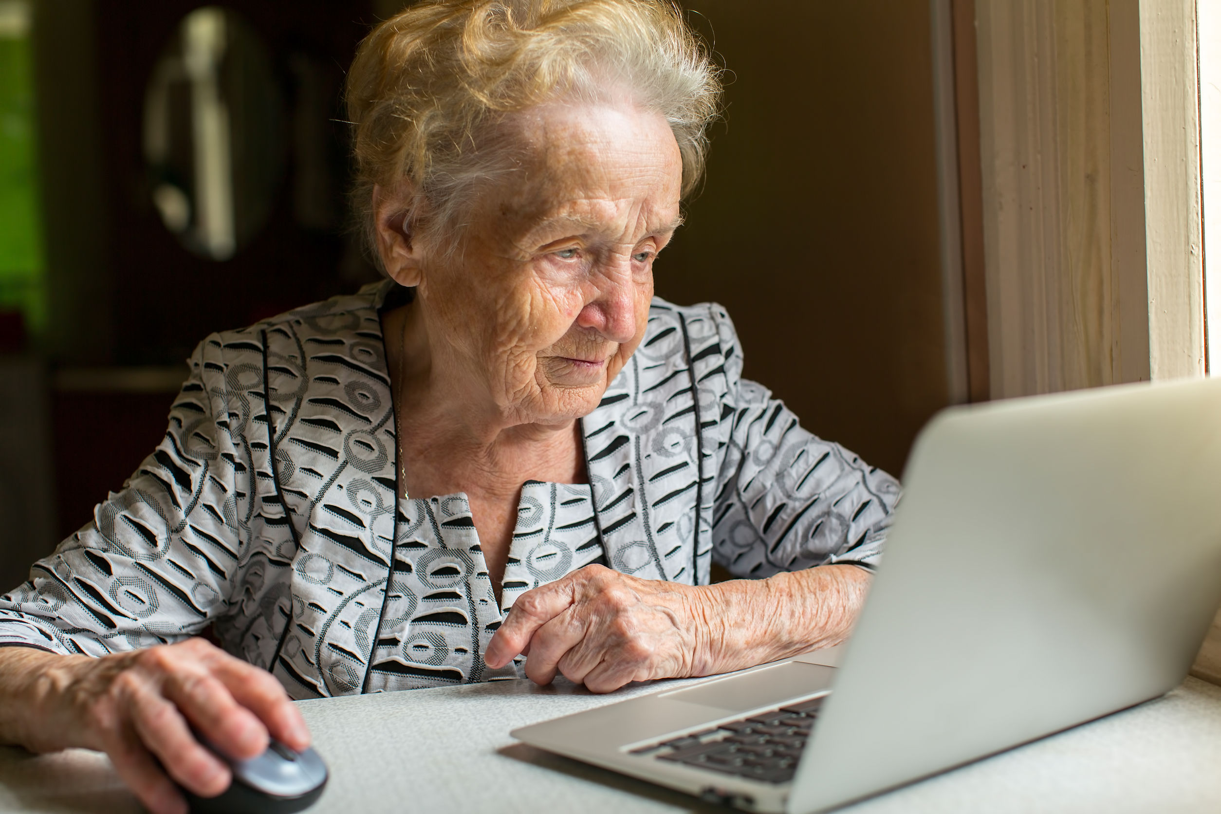 An elderly woman working on a laptop.