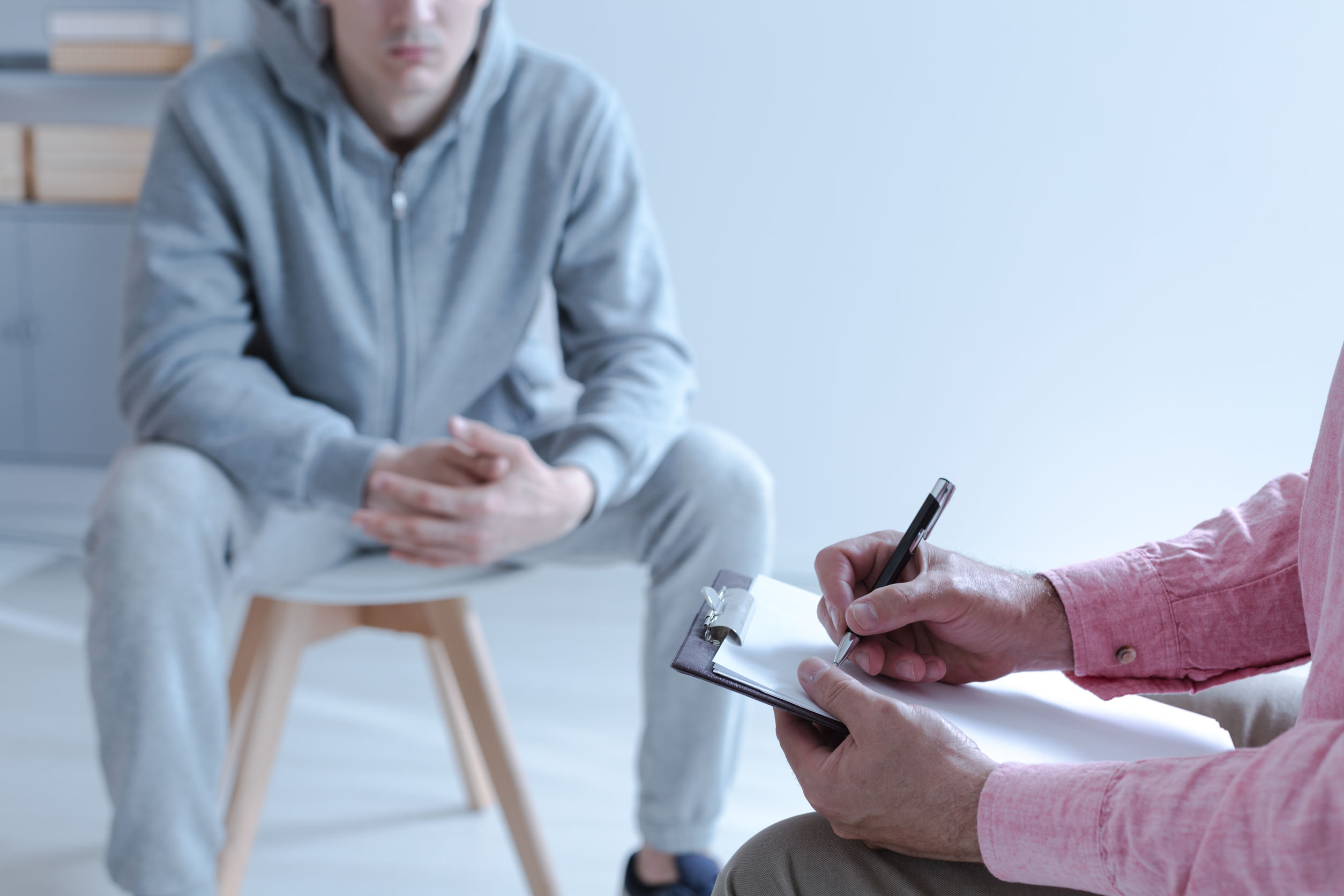 A young troubled man sitting on a chair in a blurred background. In the front hands of a therapy specialist taking notes during an individual meeting. Copy space.